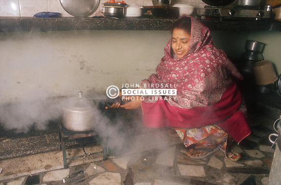 Kitchen of middleclass family in Gobindigarh; Punjab; India; with mother cooking with pressure cooker,