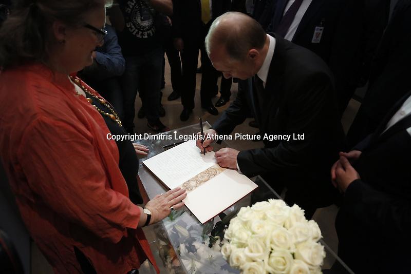 Pictured: Vladimir Putin signs the visitors' book Friday 27 May 2016<br /> Re: Russian President Vladimir Putin with Greek Prime Minister Alexis Tsipras at the exhibition opening 'Ascension of the Christ' at the Byzantine Museum, Athens, Greece