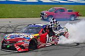 #18: Kyle Busch, Joe Gibbs Racing, Toyota Camry Skittles Red White & Blue celebrates with a burnout after winning