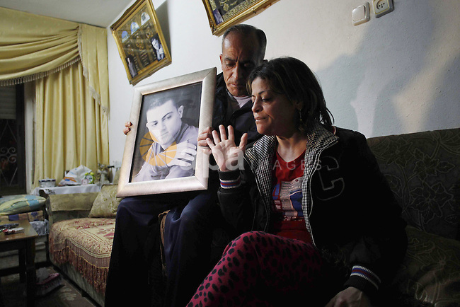 The mother and father of Muhammad Musallam, an Israeli Arab held by Islamic State in Syria as an alleged spy, react with a picture of him in their East Jerusalem home March 10, 2015. A video posted online by Islamic State militants on Tuesday showed a child killing Muhammad Musallam, an Israeli Arab accused by the group of being a Mossad spy, with a bullet to the head. Reuters could not immediately verify the authenticity of the footage, which also appeared on Twitter feeds used by Islamic State supporters. Israeli security officials said they were aware of the video but could not confirm that it was authentic. Photo by Muammar Awad
