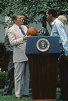 Washington DC., USA, June 13, 1984<br /> President Ronald Reagan meets with the Boston Celtics, the National Basketball Association World Champions, in the rose Garden. Coach Red Auerbach presents him with a team jacket. Credit: Mark Reinstein/MediaPunch