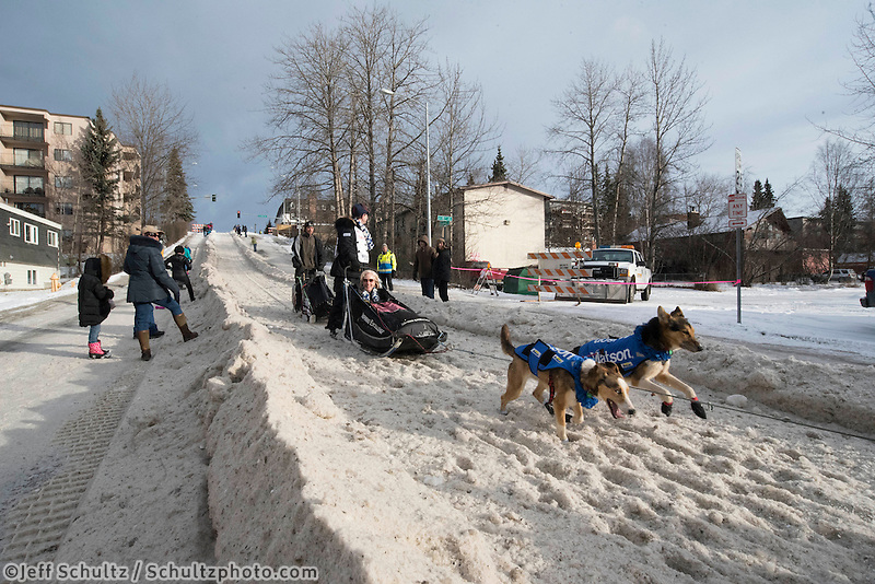 Allen Moore and team run past spectators on the bike/ski trail with an Iditarider in the basket during the Anchorage, Alaska ceremonial start on Saturday, March 5, 2016 Iditarod Race. Photo by O'Hara Shipe/SchultzPhoto.com