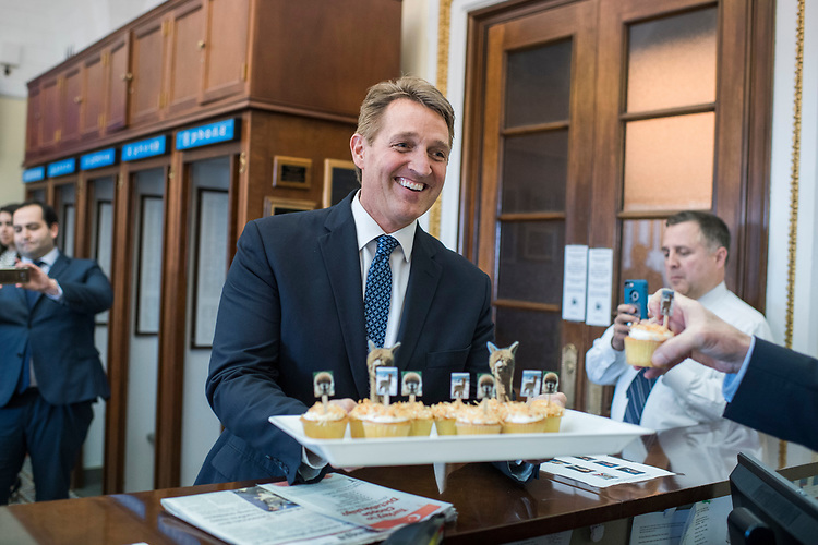 "UNITED STATES - APRIL 5: Sen. Jeff Flake, R-Ariz., hands out alpaca themed cupcakes and copies of his seventh oversight report titled ""Tax Rackets: Outlandish Loopholes to Lower Tax Liabilities,"" to reporters and staff in the Capitol press gallery, April 5, 2017. One loophole cites individuals owning alpacas to use as tax write-offs. (Photo By Tom Williams/CQ Roll Call)"