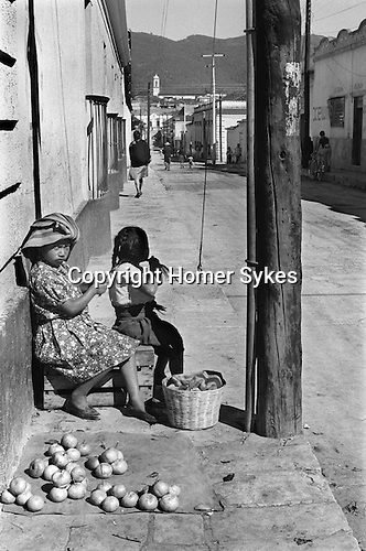 San Cristóbal de las Casas, Mexico. Indigenous  Indian girl child and sibling selling apples in the street. 1973.