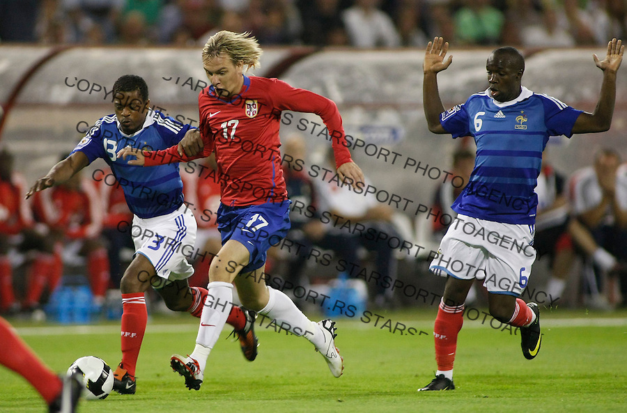 Serbia's player Milos Krasic, center, in action against France players Patrice Evra, left and Lassana Diarra, right, during their World Cup 2010 qualifying soccer match between Serbia and France, at Belgrade, Serbia, September 9,