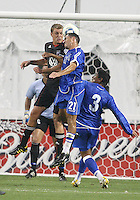 Adam Cristman #7 of D.C. United goes up for a header against Juan Carlos Moscoso #21  of El Salvador during an international charity match at RFK Stadium, on June 19 2010 in Washington DC. D.C. United won 1-0.