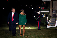United States President Donald J. Trump and First Lady Melania Trump make their way across the South Lawn of the White House after returning on Marine One from their surprise trip to Al Asad Air Base in Iraq to visit troops, in Washington, DC, USA, 27 December 2018. Photo Credit: Pete Marovich/CNP/AdMedia