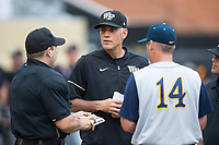 Wake Forest Demon Deacons head coach Tom Walter (16) exchanges lineup cards with home plate umpire Ryan Morehead and West Virginia Mountaineers head coach Randy Mazey (14) prior to Game Six of the Winston-Salem Regional in the 2017 College World Series at David F. Couch Ballpark on June 4, 2017 in Winston-Salem, North Carolina.  The Demon Deacons defeated the Mountaineers 12-8.  (Brian Westerholt/Four Seam Images)