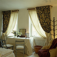 Double tie-back curtains are a feature of this guest bedroom