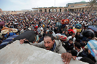 People try to climb a wall at the border crossing.Tens of thousands of people, mainly Egyptian workers, flee unrest in Libya and cross the border into Tunisia. Some slept in the open for several days before being processed.  At the same time forces loyal to Col. Gaddafi fought opposition forces in various parts of the country.