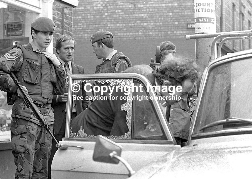 British soldiers and detectives at the assasination scene of Billy McMillen, aka Liam McMillen, officer commanding, Official IRA, ORA, in Belfast, N Ireland.  McMillen was shot dead 28th April 1975 as he sat in his car in Spinner Street, off the Falls Road, after collecting his wedding photographs from nearby premises. His wedding had taken place 6 weeks previously. See Lost Lives 1370 for more information. His wife, Mary, nee McGovern, also in the car, was uninjured. 197504280250. <br />