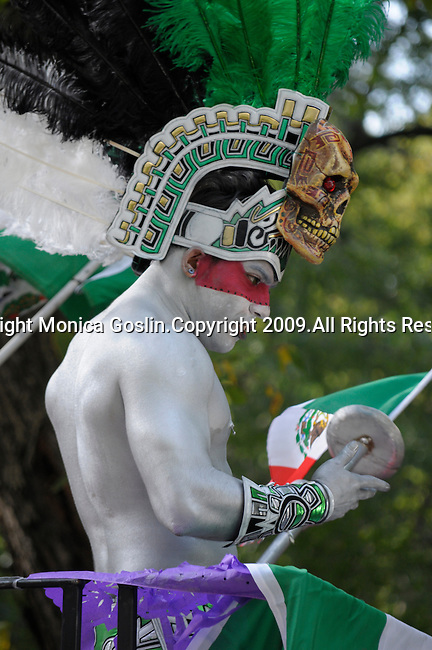 The Hispanic Parade in New York City. A man painted silver and wearing a head dress represents Mexico in the Hispanic Parade in New York City.