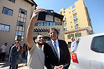 A Palestinian man takes a selfie with Dutch Foreign Minister Bert Koenders in front of Roots Hotel in Gaza City on July 15, 2015. Koenders, visited the Kerem Shalom Crossing in southern Israel, which borders Gaza, to inaugurate a new security scanning system. The machine was donated by the Netherlands, and aims to increase the number of trucks crossing into Gaza from Israel. Photo by Ashraf Amra