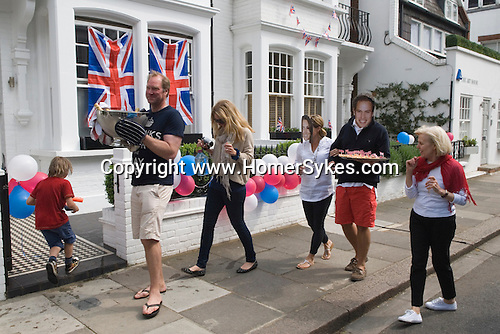 Royal Wedding Street Party. Chelsea  London. Prince William Kate Middleton Princess Catherine souvenir masks. Man carrying ice bucket with champagne. April 29 2011.