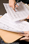 Elementary school Grade 5 arts inrichment closeup of hands, manuscript paper and musical nots as two boys work together on assignment in music theory vertical