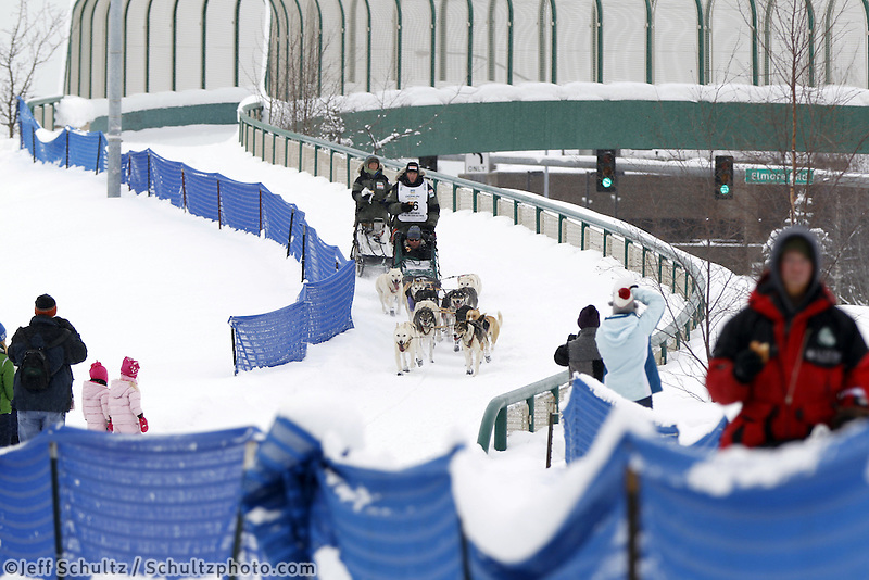 Saturday, March 3, 2012  Lachlan Clarke enjoys a hot dog while crossing the Tudor Road bridge during the Ceremonial Start of Iditarod 2012 in Anchorage, Alaska.