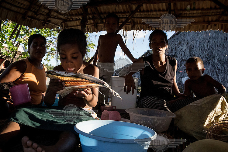 Esata, six, eating a dry fish while sitting with her family in their home. Her mother says: 'Every high tide water comes to our house. Many families already moved, only three houses left. We are almost the last people that stay in this area. Soon the ocean will force us to leave this place.' The country's government says Tebunginako is a 'barometer for what Kiribati can expect in the future'. Since the 1970s the village's residents have seen the sea levels rise and eventually erosion has meant that a major part of the village has had to be abandoned.