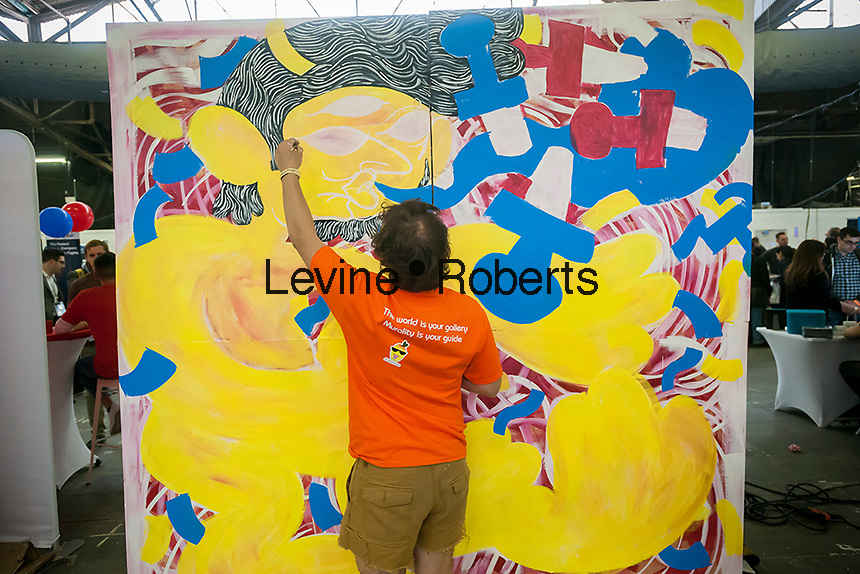 Stephen Michael Haas creates a mural for Murality at the TechDay New York event on Tuesday, April 18, 2017. Thousands attended to seek jobs with the startups and to network with their peers. TechDay bills itself as the U.S.'s largest startup event with over 500 exhibitors. (© Richard B. Levine)