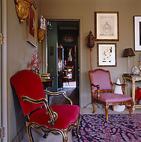 The swirling pattern and colour of a contemporary rug in the living room complement the carved antique chairs