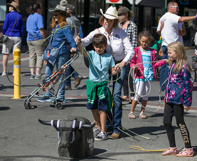 Laura Pierce helps seven-year-old Maverik learn rope tricks during the Reno Rodeo Parade on Saturday, June 22, 2019.