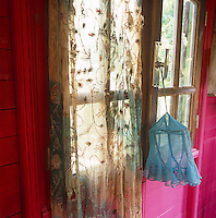 An item of blue mesh fabric is tied to the handle of a pair of part-glazed French doors with the lower half painted pink. An embroidered sheer curtain hangs at the window.