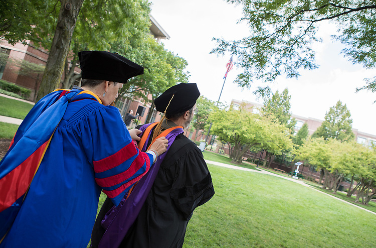 Faculty help each other straighten their hoods and robes in the Quad before processing to the 120th DePaul University Convocation on Thursday, August 31, 2017, at St. Vincent de Paul Parish. A. Gabriel Esteban, Ph.D., president, and Marten denBoer, provost, provided remarks, and many faculty and staff were recognized with annual awards including: Excellence in Teaching, Spirit of Inquiry, Excellence in Public Service, Vincent de Paul Professorship, Spirit of DePaul, Staff Quality Service, Gerald Paetsch Academic Advising and faculty promotion and tenure. (DePaul University/Jeff Carrion)
