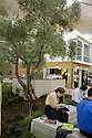 """Attendees take a break under an olive tree in the front yard of the """"Harbinger"""" house. The 1700 sq ft two-story showhouse built from reused shipping containers is quite an attraction on the tradeshow floor. It was designed by The Lawrence Group and built by SG BLOCKS(tm). West Coast Green is the nation?s largest conference and expo dedicated to green innovation, building, design and technology. The conference featured over 380 exhibitors, 100 presenters, and 14,000 attendees. Location: San Jose Convention Center in Silicon Valley (San Jose, California, USA), September 25-27, 2008"""