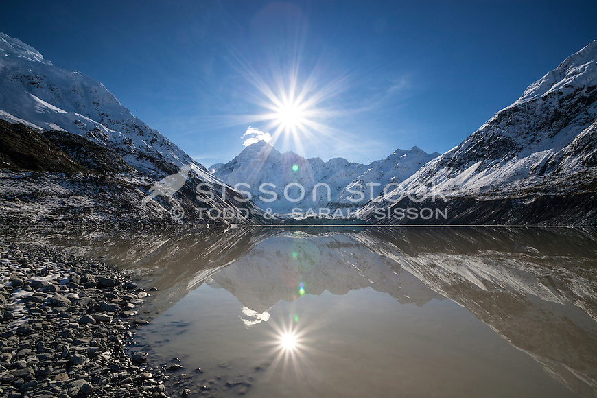 New Zealand Stock Photo - Aoraki Mt Cook reflected in Hooker Lake on a pristine blue sky day. Sunstar & lens flare.