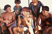 Pavuru Village, Brazil. Village man with red urucum dyed hair inspecting a camera.