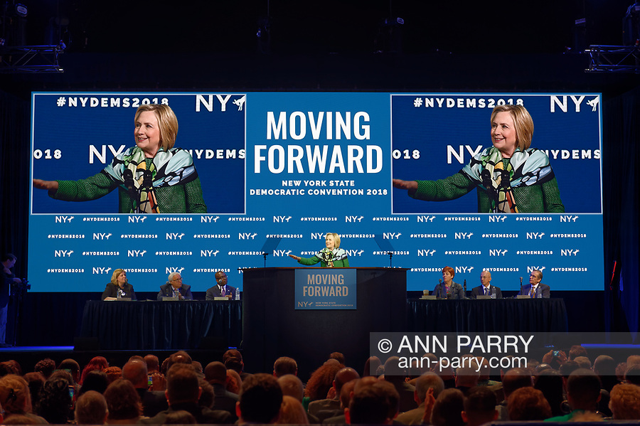 Hempstead, New York, USA. May 23, 2018. HILLARY CLINTON delivers Keynote Address during Day 1 of New York State Democratic Convention, held at Hofstra University on Long Island. NYS Democratic Leaders on stage include CHRISTINE QUINN, Exec. Committee Chair, sitting to right of Clinton.