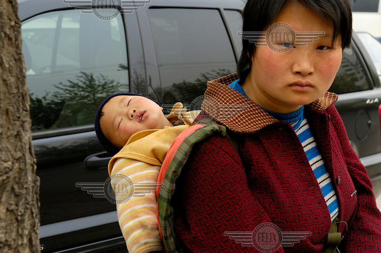 A young mother carries her sleeping child on her back.