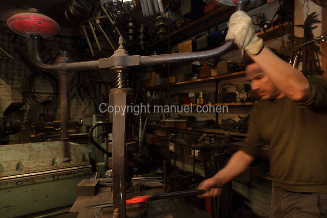 Nicolas Desbons, metalworker and artist, shaping a heated steel rod by the forge in his Soleil Rouge workshop, photographed in 2017, in Montreuil, a suburb of Paris, France. Desbons works mainly in steel but often in conjunction with other materials such as fibreglass, glass and clay, using both cold metal and forge techniques. He produces both figurative and abstract sculptures as well as furniture and lighting. Picture by Manuel Cohen