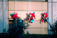 Uniformed Japanese workers clean the exterior windows of an office building. Tokyo, Shinjuku district, japan.