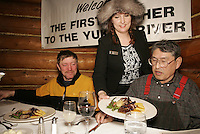 Brooke McGrath serves Paul Gebhart part of his 7-course meal by the Millenium hotel in Ruby for being the first musher to the Yukon River.  Paul's dining guest is 1975 Iditarod champion Emmitt Peters of Ruby.