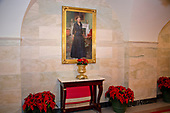 """The 2017 White House Christmas decorations, with the theme """"Time-Honored Traditions,"""" which were personally selected by first lady Melania Trump, are previewed for the press in Washington, DC on Monday, November 27, 2017.  Poinsettia plants are under the official portrait of former first lady Laura Bush in the Ground Floor Corridor.<br /> Credit: Ron Sachs / CNP"""