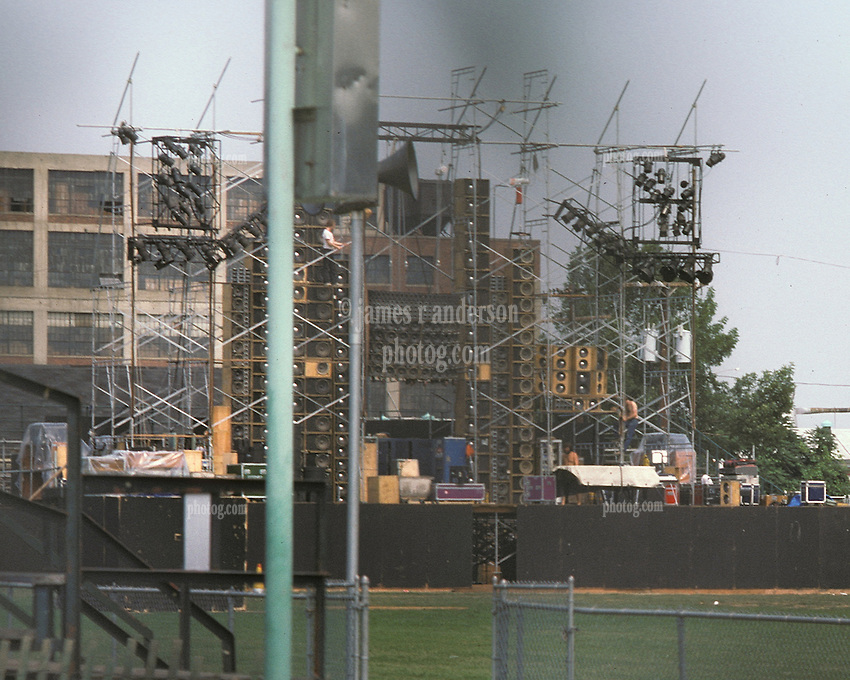 Crews setting up in an Empty Dillon Stadium the Wall of Sound before the Grateful Dead Play Live in Hartford, CT on 31 July 1974. Shot early in the afternoon, before the wind protection scrim was hung and through the fence, thus the dark areas in the frame. This is a Tighter Crop of the first frame in this gallery.