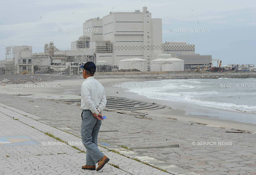 July 22nd, 2011, Fukushima, Japan - A Elderly tsunami survivor walks along a beach in front of the thermal power plant, July 22, 2011, in tsunami devastated Minamisoma city, Fukushima prefecture, northeastern Japan, about 20km away from the tsunami-crippled Fukushima Daiichi Nuclear Power Plant. According to Japan's Kyodo news, the Japanese government will need to spend at least 23 trillion yen ($291 billion) on reconstruction projects over the next decade following the March 11 earthquake and tsunami, and is planning to expend around 80 percent of the funds during the first half of the period, officials said July 21. (Photo by Tomoyuki Kaya/AFLO)