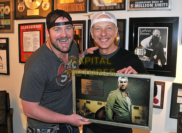 "LEE BRICE & STONEY RICHARDS.National Country Music artist LEE BRICE and radio disc jockey STONEY RICHARDS poses with a plaque presented to Richards to commemorate the record-breaking single ""Love Like Crazy"" by Lee Brice, Pittsburgh, PA, USA..March 9th, 2011               .half length grey gray t-shirt baseball cap hat backwards stubble facial hair white black          .CAP/ADM/JN.©Jason L Nelson/AdMedia/Capital Pictures."
