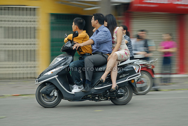 Asia, Vietnam, Hanoi. Hanoi old quarter. Family on motorbike rushing through Hanoi.
