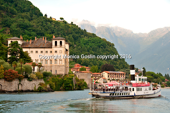 "Ferry boat named ""Milano"" on Lake Como, Italy with a view of the Palazzo Gallio in Gravedona and the Italian Alps in the background at sunset"