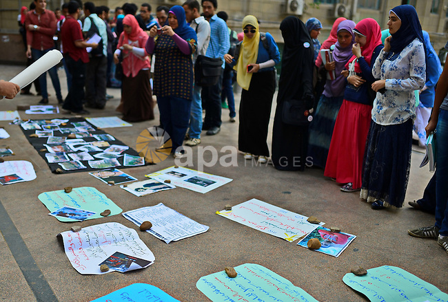 Egyptian stand looking at pictures and placards laid on a street in a show held by students against the arrest of the students of Universities, and against the military rule, outside Cairo University on November 05, 2014. Photo by Amr Sayed