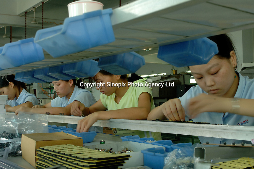 Workers at an electronics factory in Shenzhen, China, hand assemble circuit boards for use in DVD players. Shenzhen Special Economic zone is one of the world's most intensive and dense manufacturing areas..