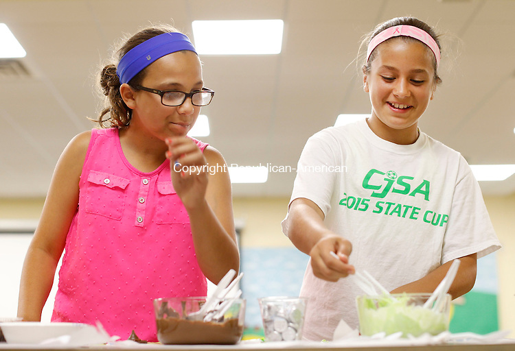"Middlebury, CT- 23 June 2015-062315CM04- Isabella Guerrera, 12, left, and Amanda  Graziano, 12, both of Middlebury, work on an edible witches made out of sweets at the Middlebury Public Library on Tuesday.   The project was part of the library's summer reading program, themed ""The Wizard of Oz"" said Jessie DeMayo, teen librarian.  The witches were made out of chocolate, pretzels, Hershey Kisses, cookies and Laffy Taffy.   Christopher Massa Republican-American"