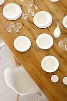 The solid oak dining table is covered in plates and glassware and flanked by Charles Eames dining chairs