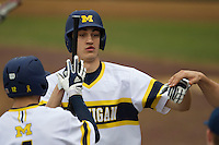Michigan Wolverines outfielder Jackson Lamb (10) is greeted by his teammates after a sacrifice bunt during the NCAA baseball game against the Washington Huskies on February 16, 2014 at Bobcat Ballpark in San Marcos, Texas. The game went eight innings, before travel curfew ended the contest in a 7-7 tie. (Andrew Woolley/Four Seam Images)