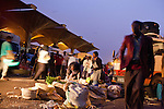 Traders and buyers bustle in the early dawn at Nairobi's Wakulima market.