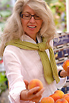 A woman in glasses searching through some apricots at the market.
