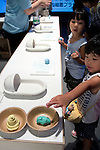 """Children see a human feces made by plasticine at the Toilet!? Human Waste & Earth's Future exposition on August 1, 2014 in Tokyo, Japan. The Toilet!? Human Waste & Earth's Future is an exposition to listen the toilet's voice and explore what is the """"happy toilet"""" for each human being on the earth at National Museum of Emerging Science and Innovation in Tokyo from July 2 to October 5. The toilet is related not only to our daily life but also to the global environment. The exposition consist of eight areas where you can learn toilet problems for each generation and in the world. (Photo by Rodrigo Reyes Marin/AFLO)"""