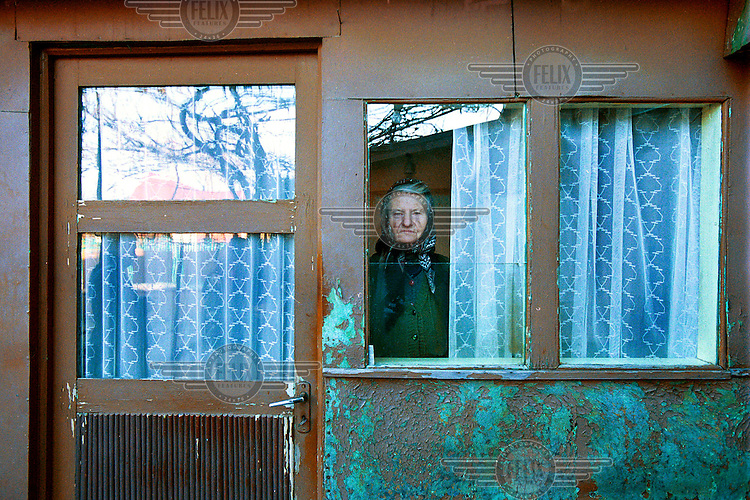 "Olga Bejenaru (80), a widowed housewife. She lives in the garage next to her old house. ""My husband got ill. Because of the doctors' bills we ran into debts and had to sell our house."" Every summer she makes wine and jam. ""With this money I can pay the heating bill for half of the winter."""