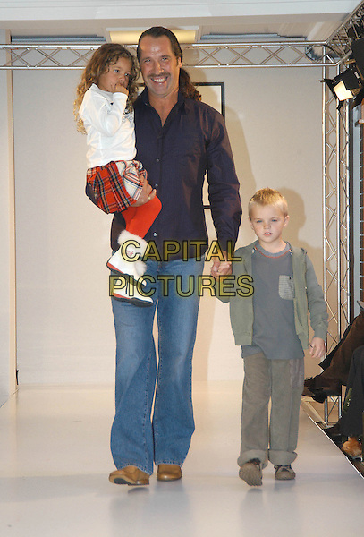 "DAVID SEAMAN.As part of Made In Italy (6th September to the 30th October) at Harrods, celebrity Dad takes part in a  dazzling D&G (Dolce & Gabbana) childrenÕs fashion show in association with ""Vogue Bambini"" and BarnardoÕs at Harrods, Knightsbridge, London, October 1st 2004..full length son daughter children catwalk.Ref: HT.www.capitalpictures.com.sales@capitalpictures.com.©Capital Pictures."